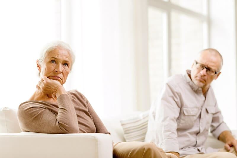 Unhappy older caucasian couple sitting on the couch