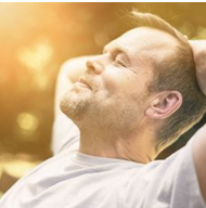 Adult caucasian male sitting on a bench relaxing with his head back and eyes closed