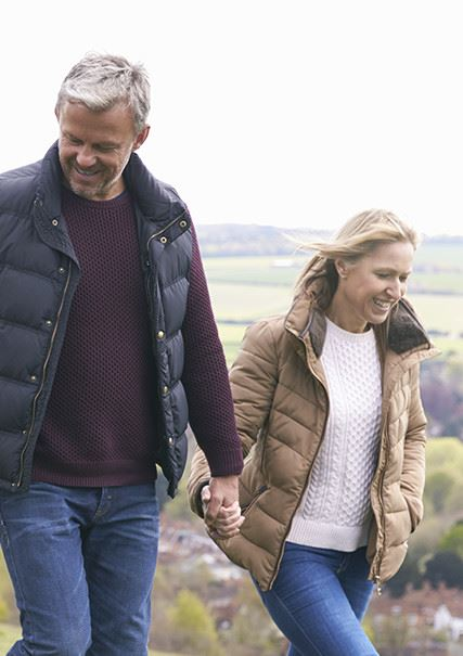 An older caucasian couple walking while holding hands